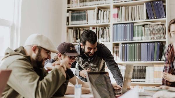 Un gruppo di amici lavora insieme allo stesso computer con entusiasmo